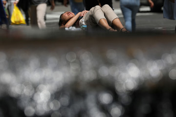 A woman lies in the midday sun near a fountain as temperatures soared across the northeast United States in Manhattan in New York City