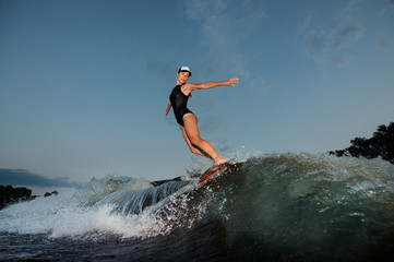Young athletic nice woman riding on the orange wakesurf