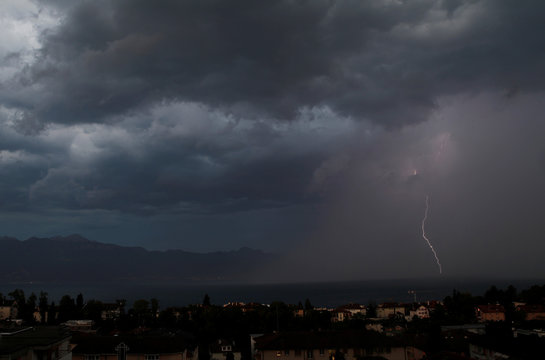 A lightning strikes on Lake Leman during a rain storm during a heat wave in Lausanne