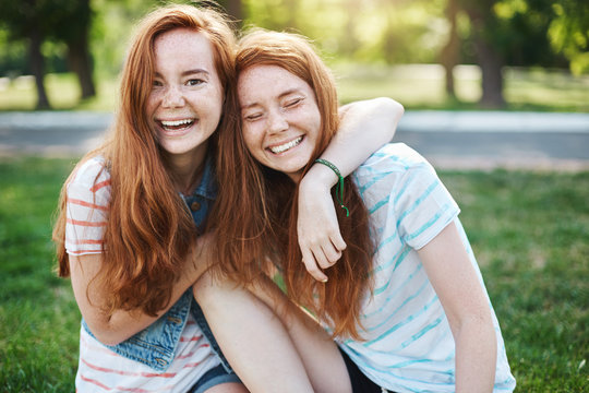 Wanna hug her forever. Portrait of happy and carefree two twin sisters with natural red hair and freckles, laughing out loud and cuddling, fooling around while resting in park on fresh green grass