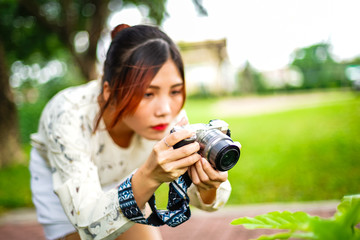 Asian girl student learn photography with small pocket camera outdoor at day in the park or university campus