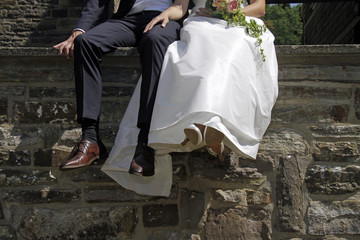 Newlyweds sitting on a wall in the sun