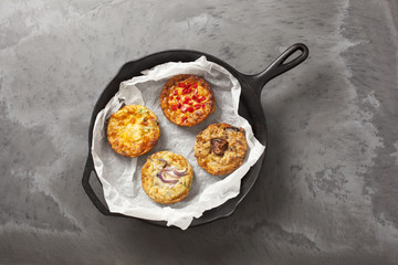 A cast iron pan containing  four freshly cooked quiches on a dark slate effect surface