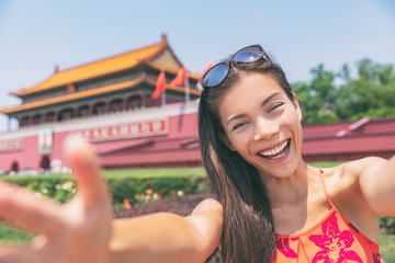 Asian tourist girl taking selfie photo with phone at Tiananmen Square in Beijing city, China. Asia travel chinese woman lifestyle.