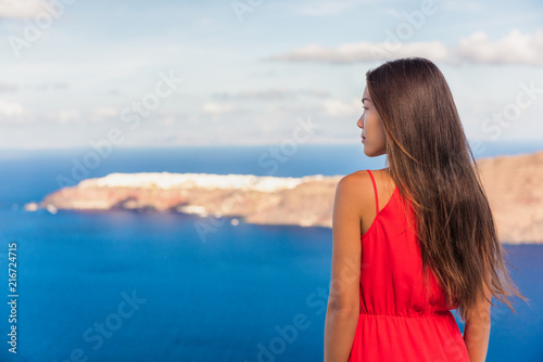 Wall mural Santorini greece travel luxury destination Asian woman beauty at Oia landscape background. Tourist girl on holiday.