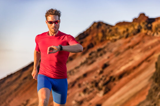 Athlete runner checking cardio on sports smartwatch jogging on outdoor run track. Running man wearing sunglasses and tech wearable device looking at watch during training workout.