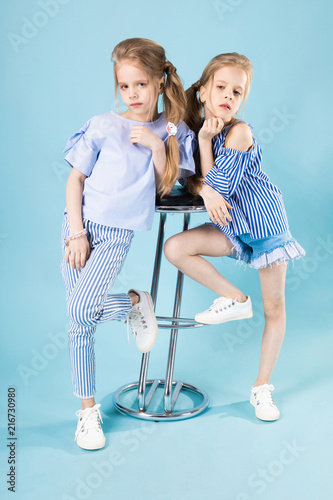 a6aa133ab Girls twins in light blue clothes are posing near a bar stool on a ...