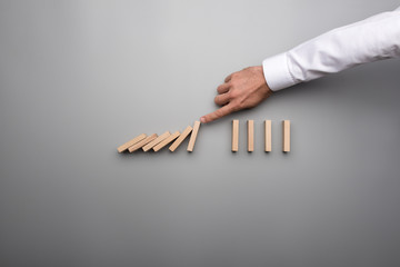 Hand of business man stopping falling domino pieces