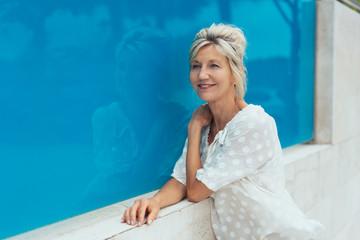 Mature smiling blonde woman against blue window