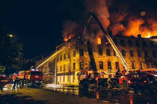 Firefighters with fire hose and fire engines or trucks are fighting fire in residential building at night. Huge smoke, flame in burning house