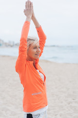 Slim healthy woman practicing yoga at the beach