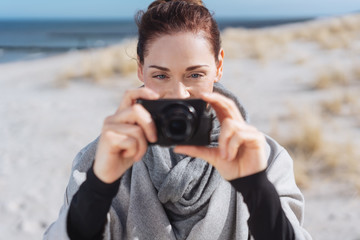 Young woman taking photographs on a beach