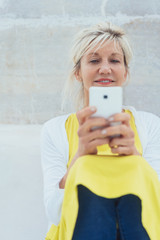 Middle-aged smiling woman using mobile phone