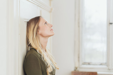 Young woman standing daydreaming indoors