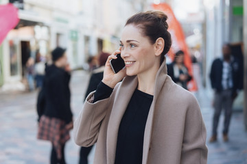 Young cheerful woman talking on phone in street