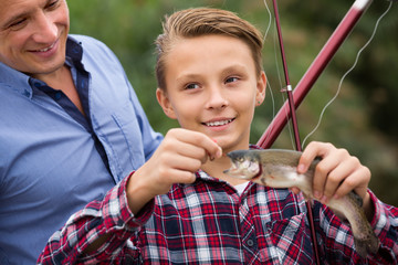 Happy man with son looking at fish on hook