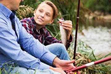 Fisher boy showing catch fish