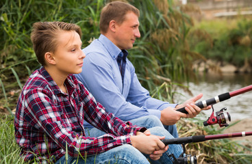 father and son fishing together on lake .