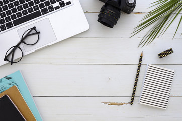 Frame made of laptop, eyeglasses, palm leaf and notebook on white wooden background. Flat lay business mockup. Freelancer workspace.