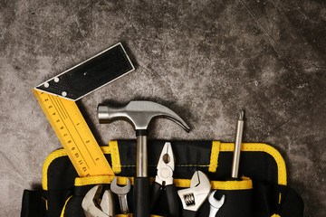 Construction worker belt with tools on concrete texture background.