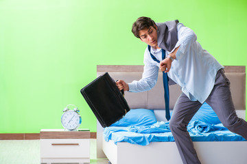 Employee in the bedroom being late for his job in time managemen
