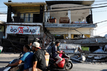 People ride motorcycles along a street next to collapsed shops after an earthquake hit on Sunday in Pemenang, Lombok island