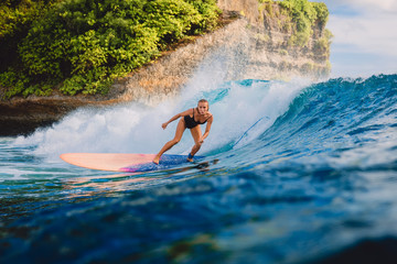 Surfer woman ride on wave surfing. Surfer and ocean wave in Bali