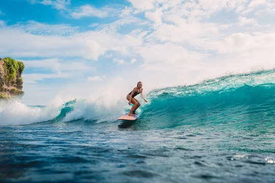 Surfer woman on surfboard during surfing. Surfer and ocean wave