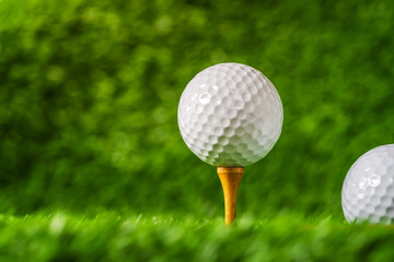 Golf ball with green grass background, on tee closeup.