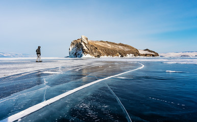Travelling in winter, a man walking on frozen lake Baikal in Siberia, Russia