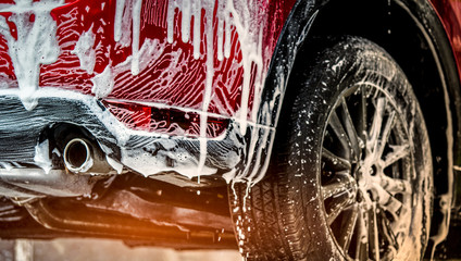 Red compact SUV car with sport and modern design washing with soap. Car covered with white foam. Car care service business concept. Car wash with foam before glass waxing and glass coating automobile.