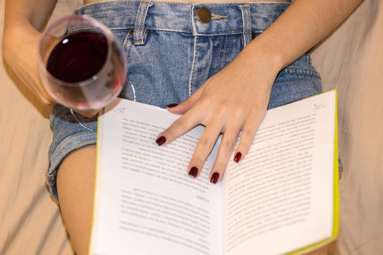 Beautiful woman relaxing taking a wine and reading a book.