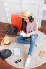 Young asian woman traveler prepare things into orange suitcase for holiday vacation at home.backpacker travel concept.