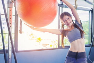 sporty woman working out with fitness ball in public gym.