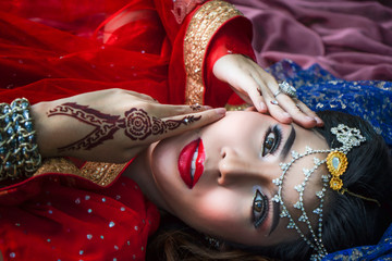 Beautiful face female with make up in Indian dress laying on floor covered with Indian cloth and smiling