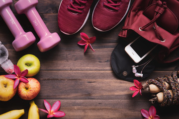 Woman active healthy lifestyle concept.  Weight and dieting concept. Creative flat lay of sport and fitness equipments  with woman accessories, apples, bottle of waters, sports shoes and dumbbells.