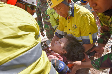 Rescue workers and soldiers carry a woman, who survived after being trapped in rubble since Sunday's earthquake, in Tanjung