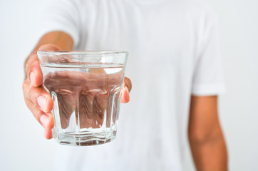 man's hand holding a glass of clean water on white background, health care concept