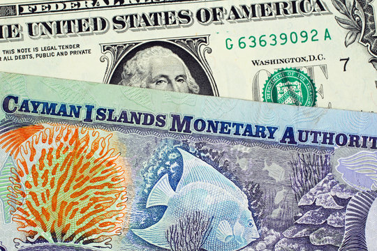 A close up image of a colorful Cayman Islands dollar bill with an American one dollar bill