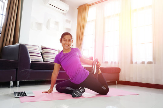 Asian women exercise doing yoga poses workout at home, With using laptop computer