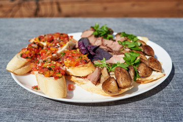 Mini sandwiches with cream cheese, mushrooms and beef. Appetizer bruschetta with chopped vegetables on  taosted baguette. Antipasti, crostini, tapas. Bruschetta with tomatoes, pepper and onion