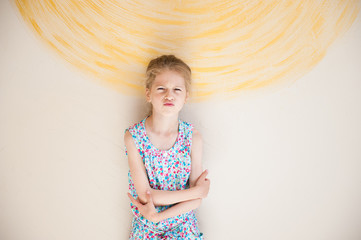 pretty upset little girl with grimace on her face vivid wall with painted sun