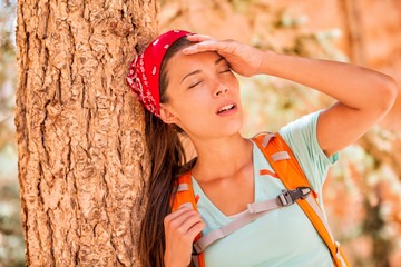 Dehydrated tired hiking woman thirsty feeling exhausted heat stroke. Girl with headache from hot temperature on outdoor activity hiker lifestyle.