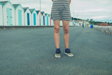 Young woman standing by beach huts