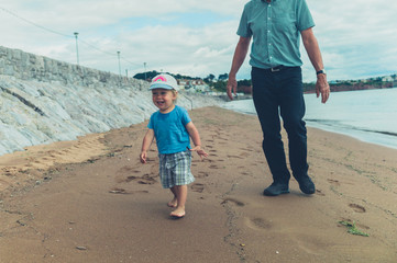 Grandfather and grandchild on the beach
