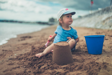 Little toddler sitting on beach with sand castle