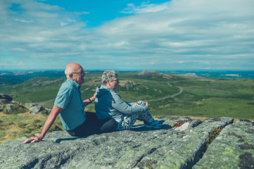 Senior couple relaxing on rock in the moor