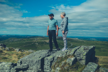 Senior couple standing on rock in the moor