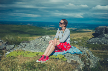 Young woman sitting on  rock in the moor