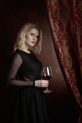 Portrait of beautiful young woman with red wine.